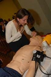 Alumni & Friends President Yvette Bocz '02 practices CPR with SimMan