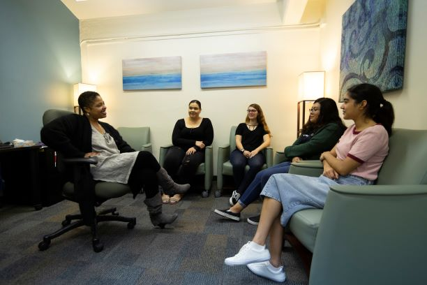 African American woman clinician sitting in a group with diverse women students