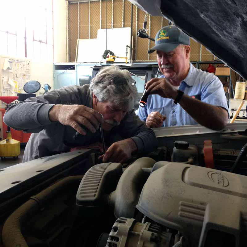 Autoshop employees working on engine