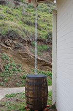 The two rain chains connected to the rain chain barrel.