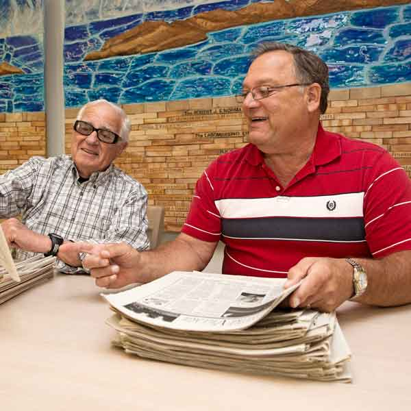 Stan Reshes (left) and Jerry Spector (right) review issues of Inside Leisure Village