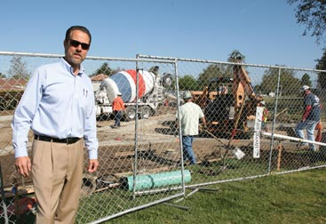 Jim Walsh poses in front of an infrastructure construction site