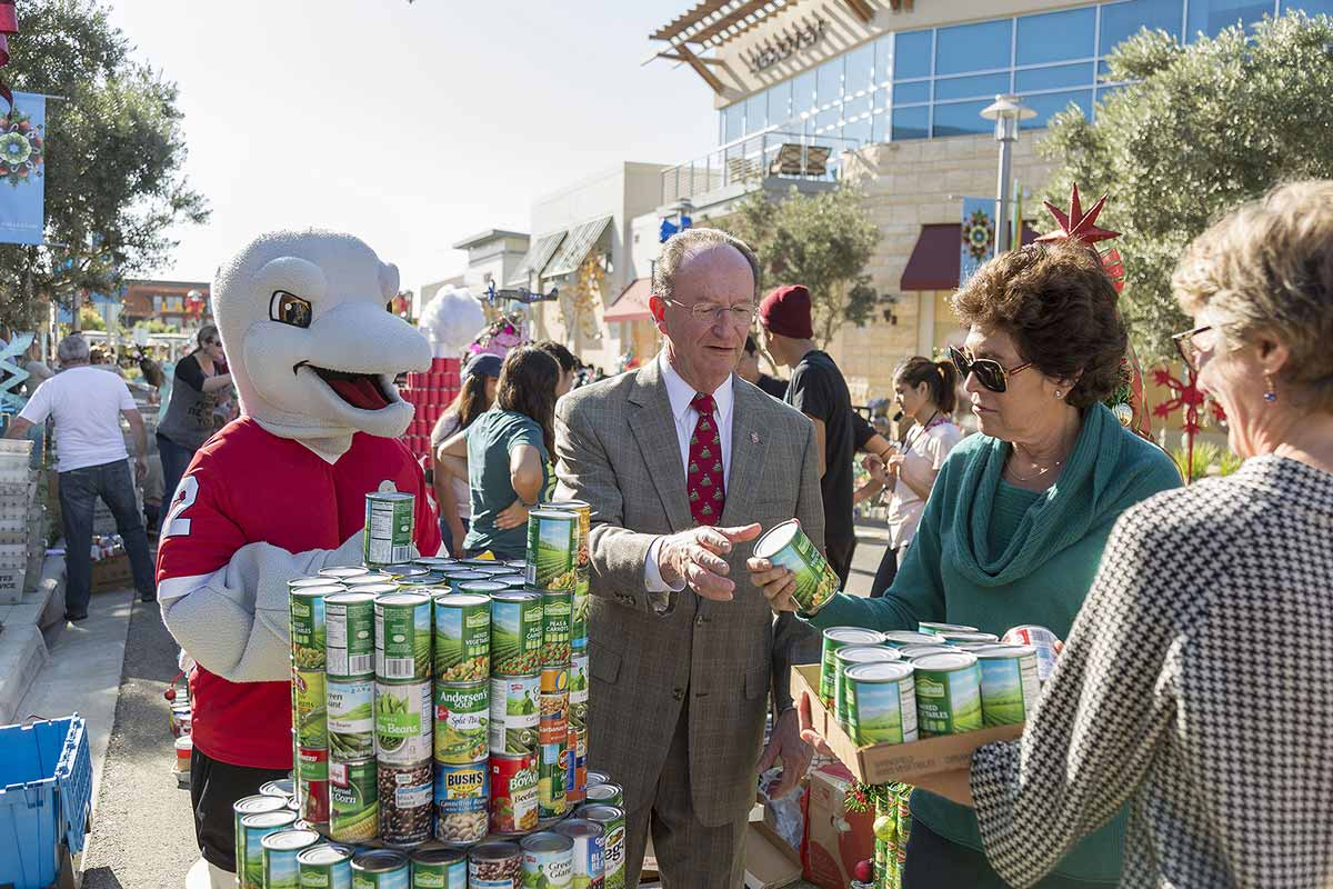University mascot, Ekho, along with President Rush and his wife, Jane, and Chief of Staff Genevieve Evans Taylor, participate in the Ventura County Food Share Can Tree Drive.