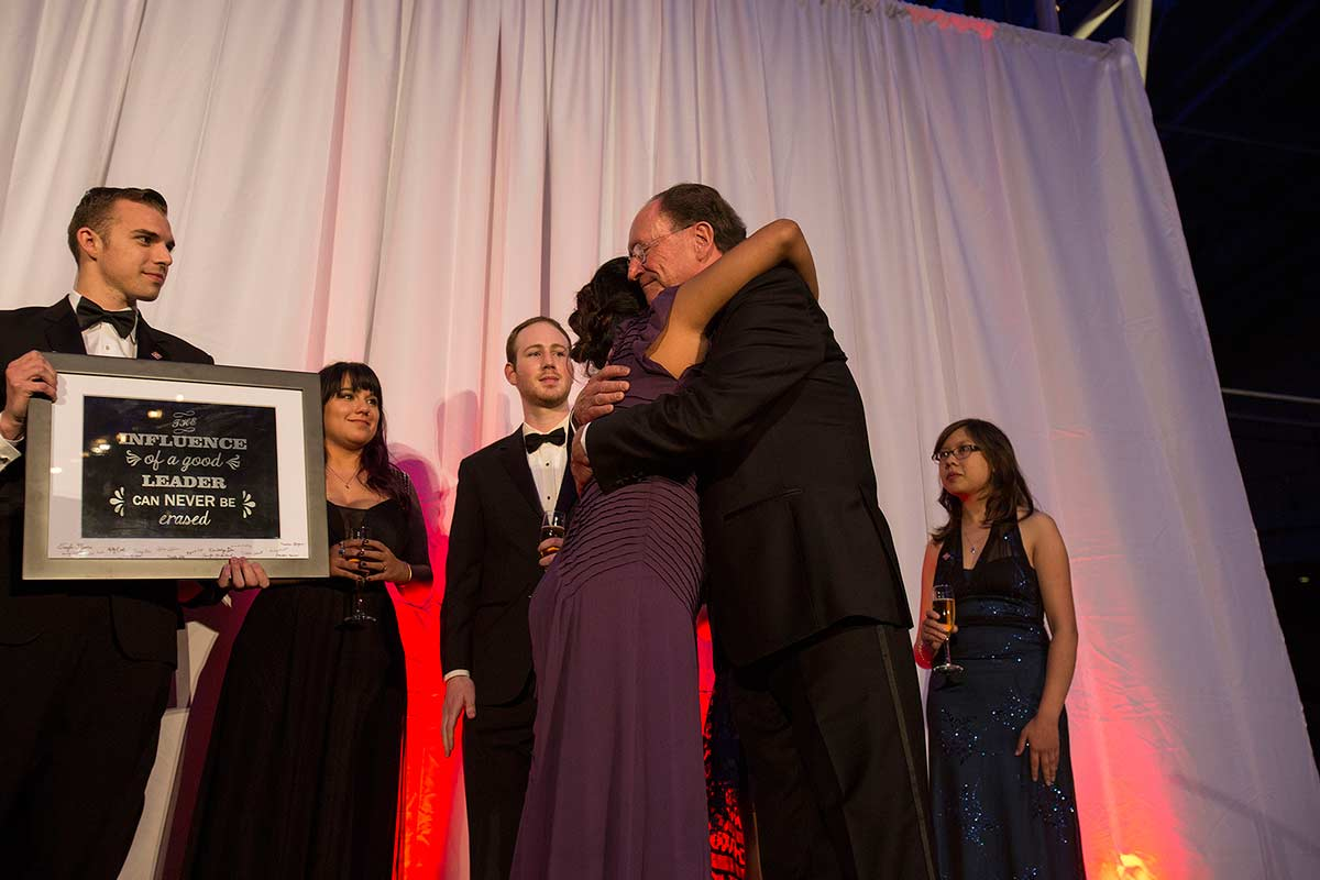President Rush receives a plaque from President's Scholars alumni at the tribute event.