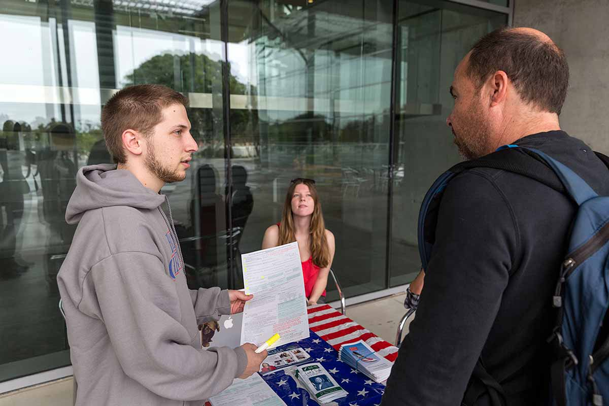Aaron Vad, president of CI College Democrats, registers students to vote during a campus registration drive.