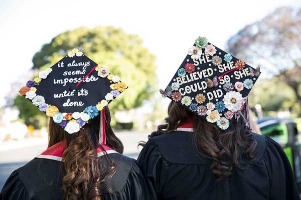 Students show off creative mortarboards.