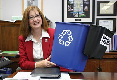 Deborah Wylie holds up a much larger recycle bin alongside a smaller trash can