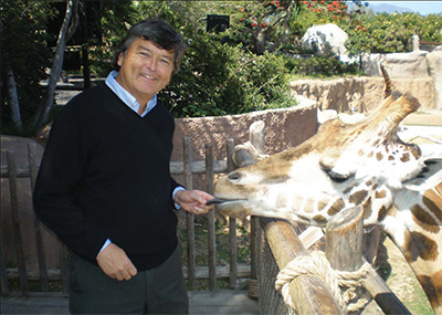 Professor Dennis Muraoka having a moment with a giraffe at the santa barbara zoo