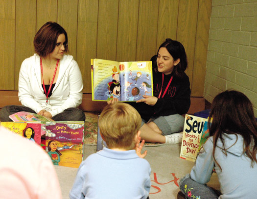 Two adults reading to children