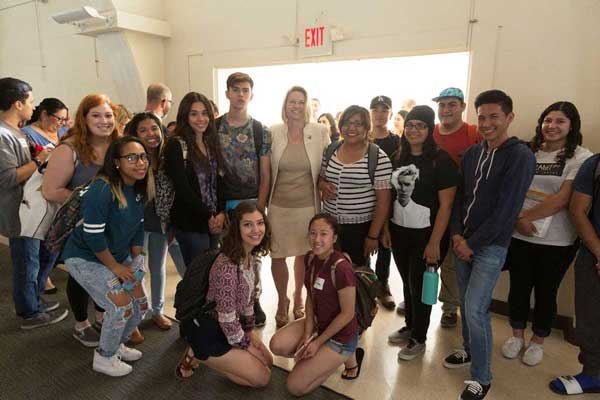 CI Students smile and pose in a group with Dr. Erika Beck during the All Campus Welcome Reception in Grand Salon.