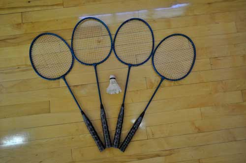Four badminton racquets and a birdie