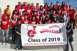 Photo of visiting students holding the Pathway to College banner.
